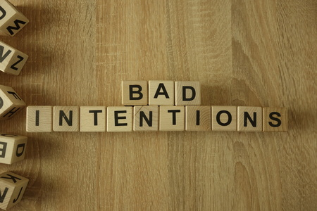 Bad intentions text from wooden blocks on desk