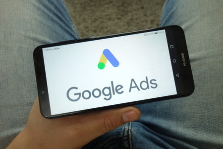 KONSKIE, POLAND - April 13, 2019: Man holding smartphone with Google Ads online advertising platform logo