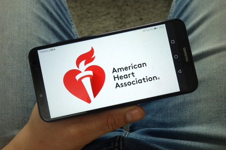 KONSKIE, POLAND - April 13, 2019: Man holding a smartphone with the American Heart Association (AHA) logo