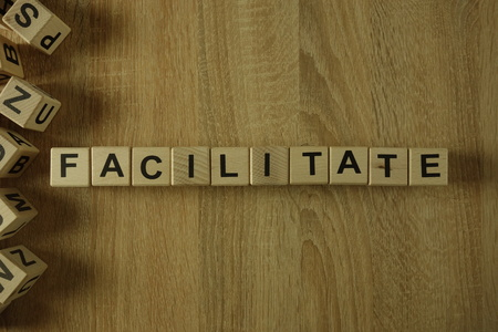 Facilitate word from wooden blocks on desk