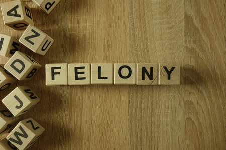 Felony word from wooden blocks on desk