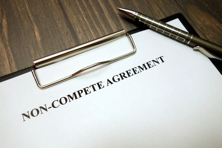Clipboard with non-compete agreement and pen on wooden desk background Banco de Imagens - 123622439