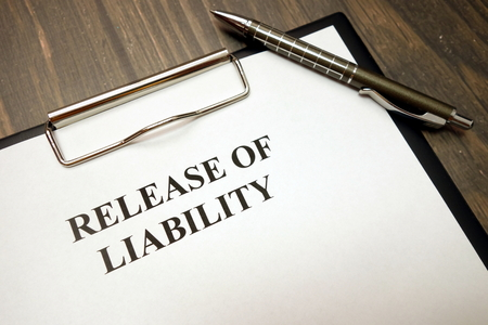 Clipboard with release of liability and pen on wooden desk background Imagens