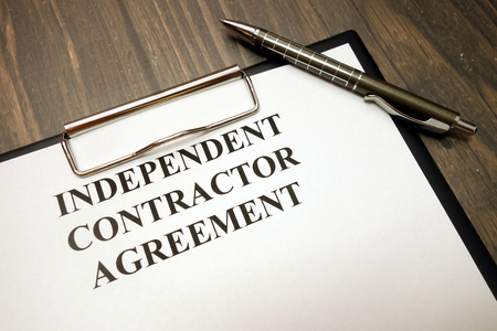 Clipboard with independent contractor agreement and pen on wooden desk background