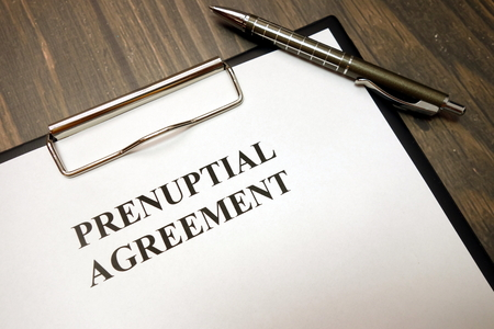 Clipboard with prenuptial agreement and pen on wooden desk background