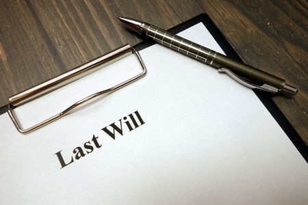 Clipboard with last will and pen on wooden desk background
