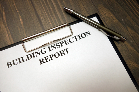 Clipboard with building inspection report and pen on wooden desk background