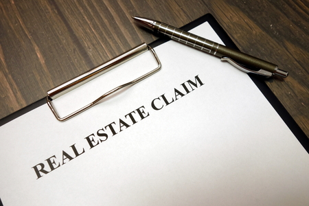 Clipboard with real estate claim and pen on wooden desk background