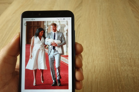 KONSKIE, POLAND - May 18, 2019: hand holding smartphone with photo of Prince Harry and Meghan Markle with baby displayed Stok Fotoğraf - 127812629