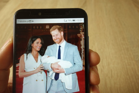 KONSKIE, POLAND - May 18, 2019: hand holding smartphone with photo of Prince Harry and Meghan Markle with baby displayed