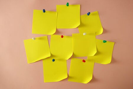 Yellow pinned sticky notes with curled corner on pink background, copy space for your design