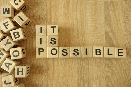 Text it is possible from wooden blocks on desk background Banco de Imagens