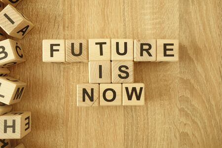 Text future is now from wooden blocks on desk background