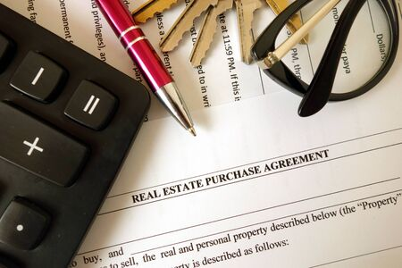 Real estate purchase agreement for filling with pen calculator keys and glasses, closeup