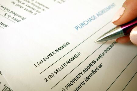 Female hand holding pen and filling purchase agreement form in office Stock fotó