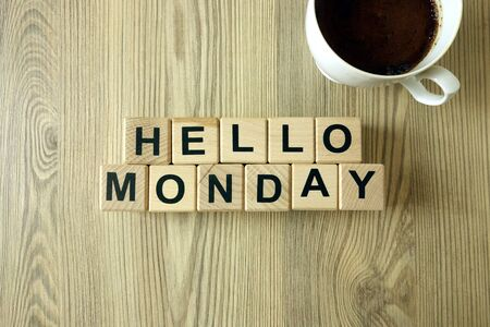 Text hello monday and cup of aromatic coffee on wooden desk background