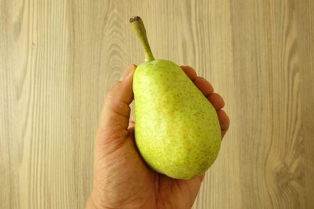 Man hand holding fresh green organic pear, closeup Reklamní fotografie - 128703082
