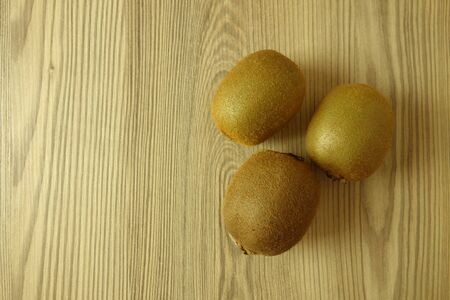 Whole kiwi fruits on rustic wooden table background, copy space for text or design Banco de Imagens