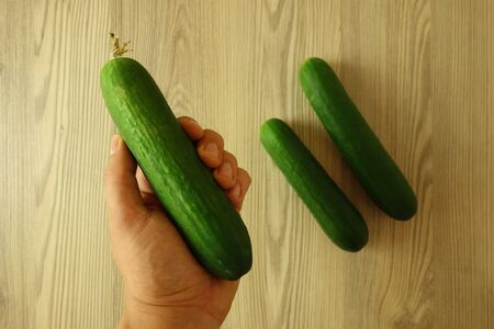 Male hand holding green juicy organic cucumber on rustic wooden background