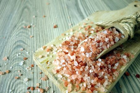 Himalayan pink salt in crystals on rustic wooden background Banco de Imagens
