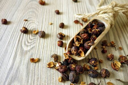 Dried hawthorn fruits in scoop on wooden table background