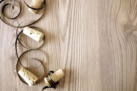 Champagne corks with ribbons on rustic wooden table, celebration background concept