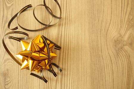 Golden star shaped festive decoration with ribbons on rustic wooden table, copy space for your design Banco de Imagens
