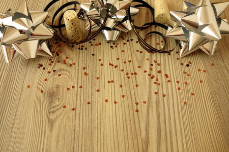 Festive decorations ribbons and confetti on wooden table background, copy space for your design