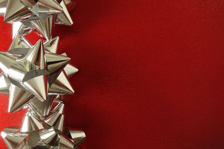 Silver star shaped decorations on red festive background with copy space for your design