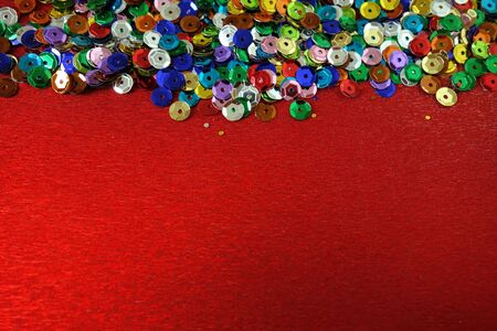 Red background with backdrop from shiny colourful decorations, copy space for your design