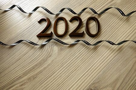 Number 2020 and ribbons on rustic wooden background, New Year party celebration concept, copy space for your design