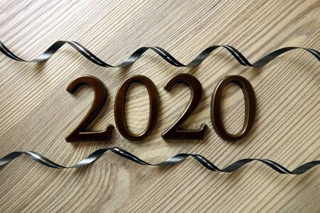 Number 2020 and ribbons on wood, Happy New Year background