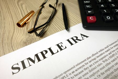 Simple ira document with pen calculator and glasses, retirement planning Stock Photo