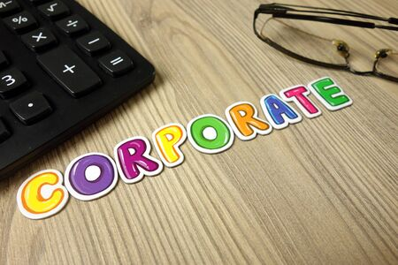 Word corporate with calculator and glasses on desk