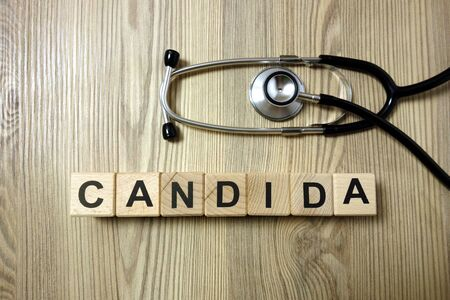 Candida word with stethoscope on wooden desk background