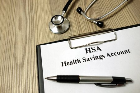 HSA health savings account paper with pen and stethoscope on wooden background Archivio Fotografico - 135270905
