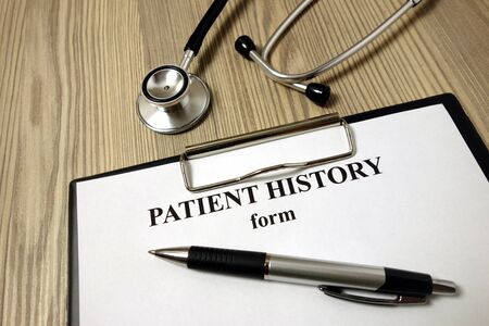 Patient history form with pen and stethoscope on wooden background Archivio Fotografico - 135270888