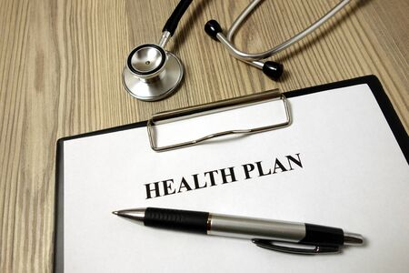Health plan paper with pen and stethoscope on wooden background Archivio Fotografico - 135270542
