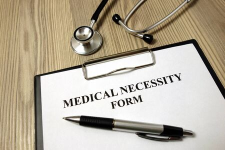 Medical necessity form with pen and stethoscope on wooden background Archivio Fotografico - 135271049