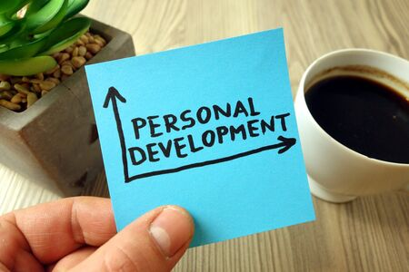 Personal development concept with text handwritten on blue sticky note