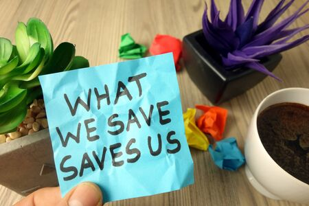 Slogan what we save saves us handwritten on sticky note, clean earth and environment protection concept