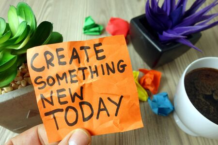 Slogan create something new today handwritten on sticky note, inspiration or motivation concept