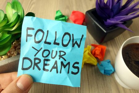 Slogan follow your dreams handwritten on sticky note, motivation and inspiration concept