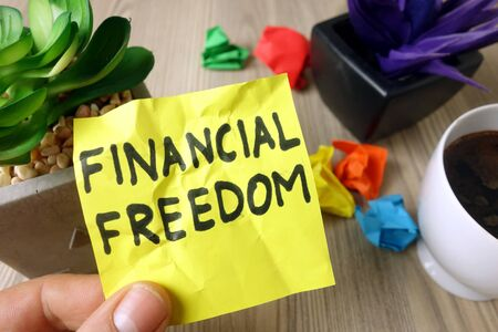 Text financial freedom handwritten on sticky note, economy success concept
