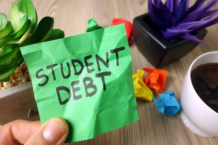 Text student debt handwritten on sticky note, financial concept