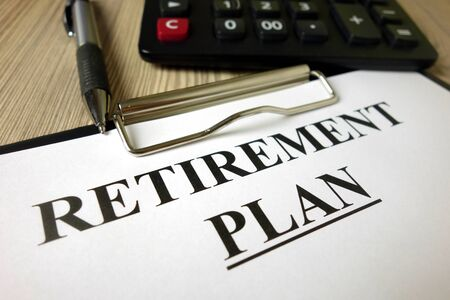 Text retirement plan on paper sheet with pen and calculator, financial concept