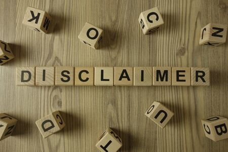 Word disclaimer from wooden blocks on desk