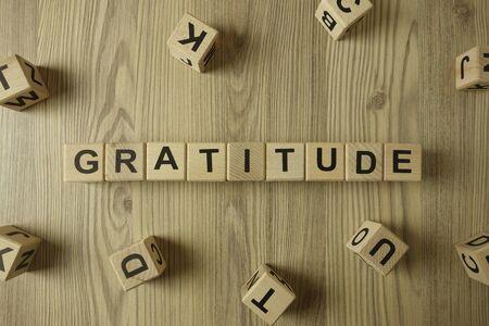 Word gratitude from wooden blocks on desk