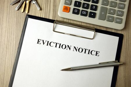 Home eviction notice document with pen calculator and keys, legal concept