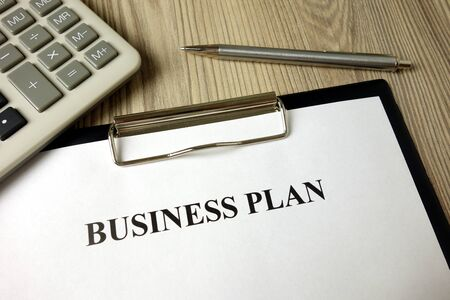 Business plan with pen and calculator, strategy management concept Standard-Bild